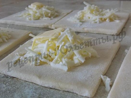 на квадраты теста кладём тёртый сыр