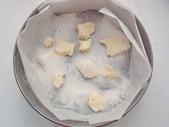 распределяем по дну формы половину сахара и кусочки масла