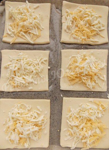 посыпаем слоёное тесто сыром и брынзой